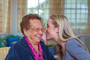 young woman whispering to grandmother